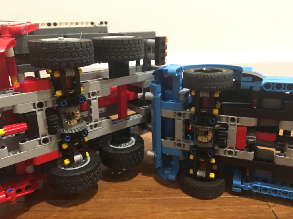 Photograph of the rear ends side by side of both the truck and the car from the LEGO Technic set 42098 Car Transporter showing a similar design for both.