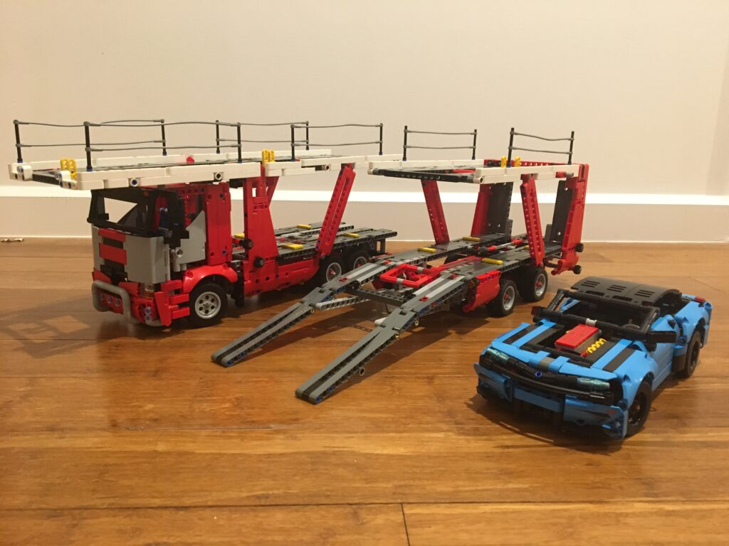Photograph of the three parts of the LEGO set 42098 Car Transporter, the red truck, the red trailer with the loading ramp open and the blue car.