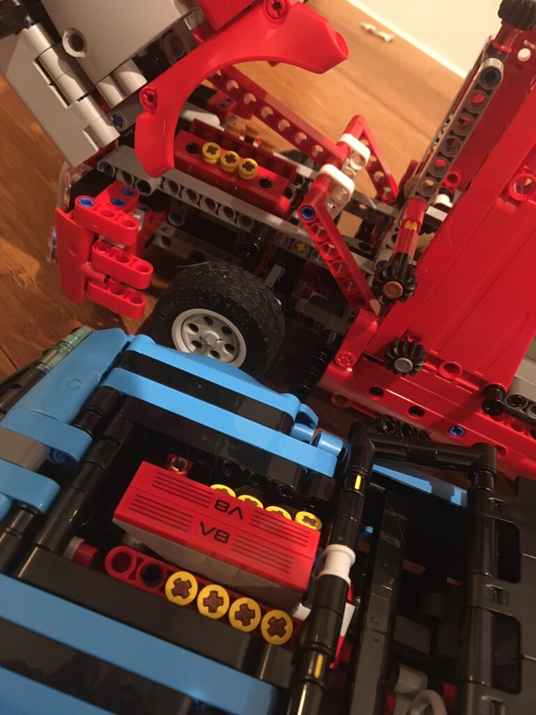 Photograph of the engines side by side of both the truck and the car from the LEGO Technic set 42098 Car Transporter showing a similar design for both.