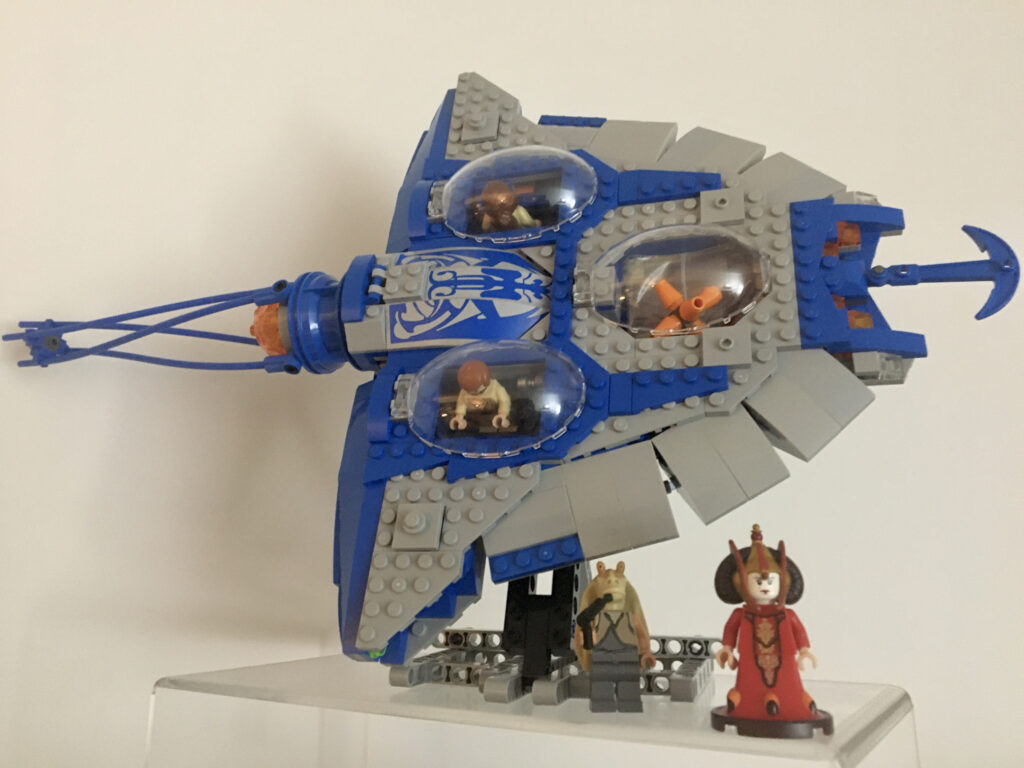 A LEGO model of the Gungan submarine featured in Star Wars Episode One displayed on an acrylic riser. The model is heavily slanted on a custom LEGO stand and lets appear the details of its top despite the picture being taken horizontally. Minifigures of Padme Amidala and Jar Jar Binks are standing next to it.