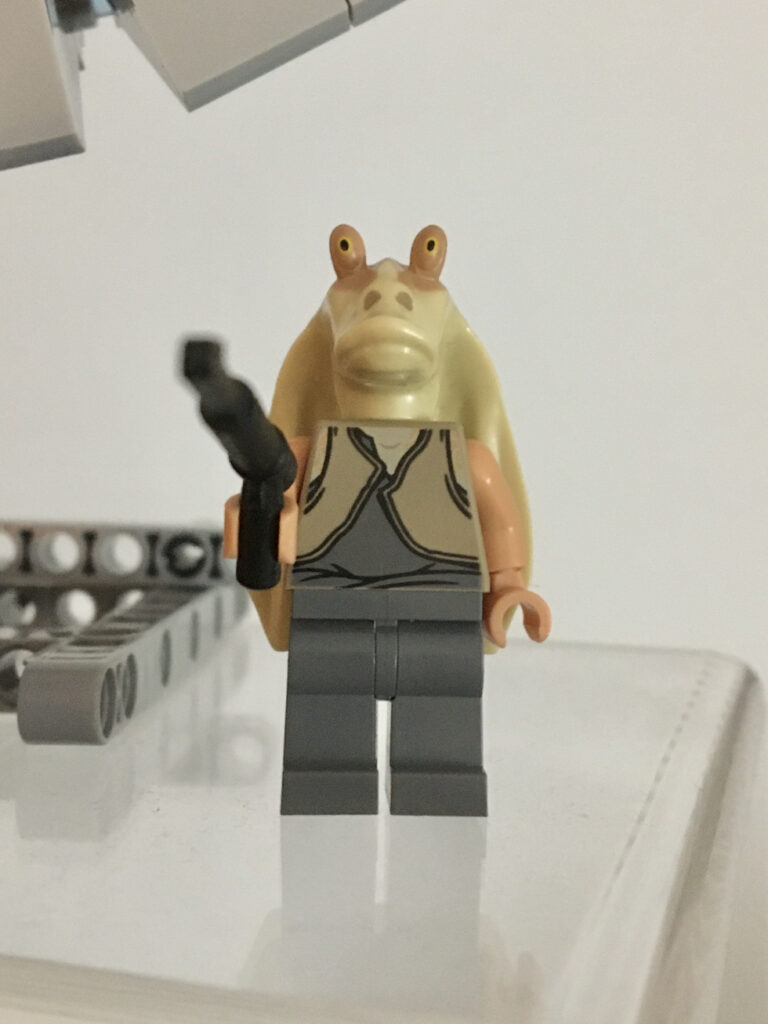 A jar Jar Binks LEGO minifigure equipped with a spear gun. His face expression is extremely serious and the face view suggests he's about to shoot the viewer.